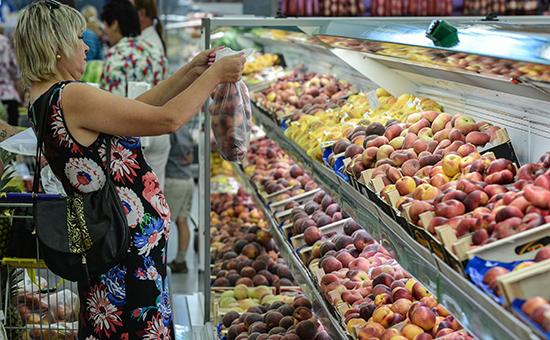 Покупательница у прилавка с фруктами