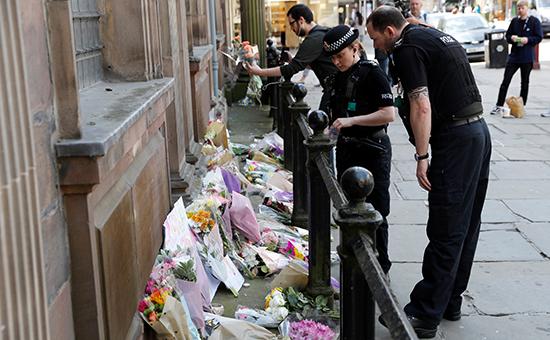 Офицеры полиции несут цветы в память о жертвах теракта