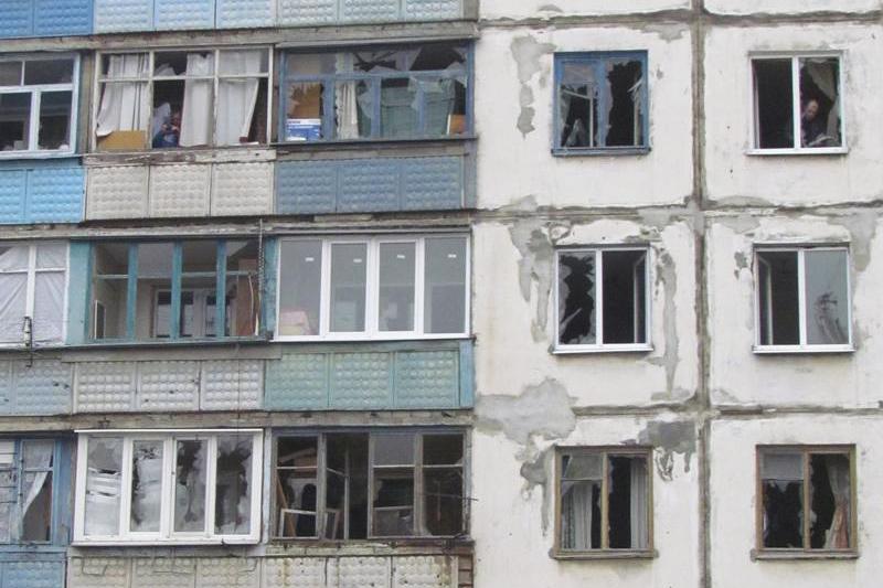 Люди выглядывают из окон жилого квартала в Мариуполе, подвергнувшегося артобстрелу