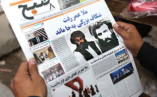 Афганец читает местную газету спортретом лидера «Талибана» муллой Ахтаром Мансуром напервой полосе. Фото: август 2015года
