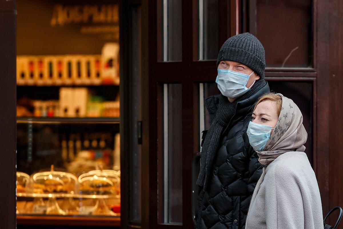 Россия. Москва. Люди в защитных масках у входа в магазин на одной из улиц города