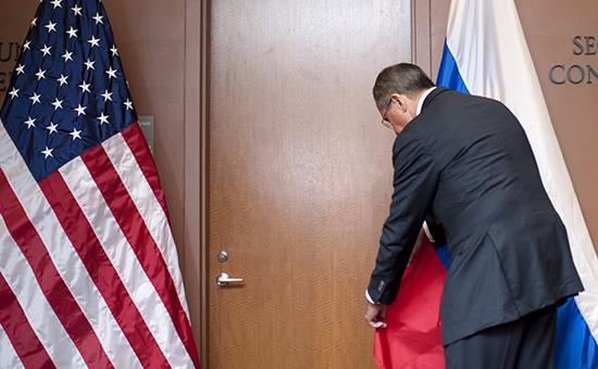 Министр иностранных дел России Сергей Лавров поправляет российский флаг перед пресс-конференцией с Джоном Керри