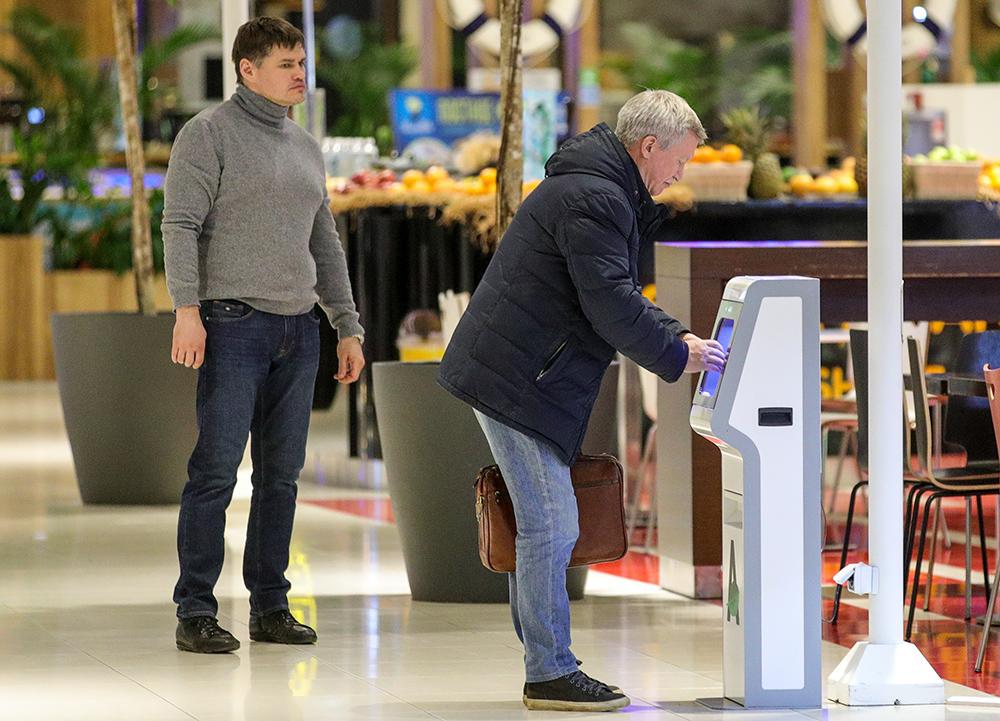 Посетители торгово-развлекательного центра «Авиапарк» возле автоматического дезинфектора рук