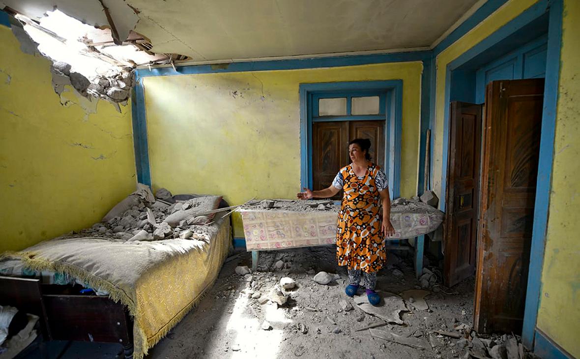 Местная жительница показывает повреждения в своем доме после обстрела армянскими войсками в Товузском районе Азербайджана