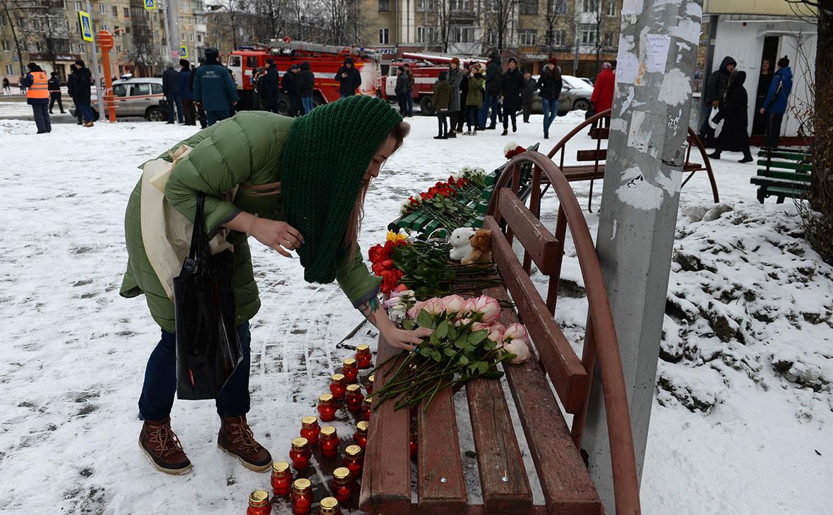 Люди несут цветы и свечи к зданию торгового центра «Зимняя вишня» в Кемерово, где произошел пожар