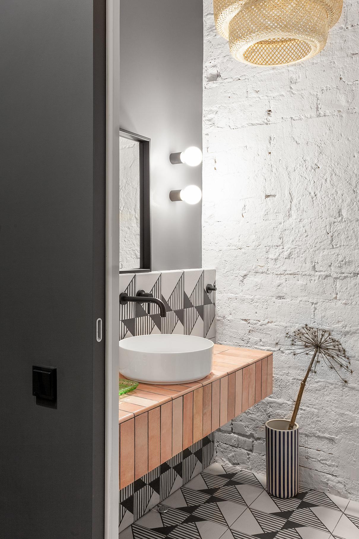 В гостевом санузле решили не оштукатуривать одну из стен и просто покрасили кирпичную межквартирную перегородку. Самодельная столешница облицована керамической плиткой Equipe коллекции Artisan. Пол и фрагмент стены— Equipe Caprice deco Origami, бра— Faro, зеркало и потолочный светильник— IKEA, раковина— CIELO, черная сантехника— BONJIO