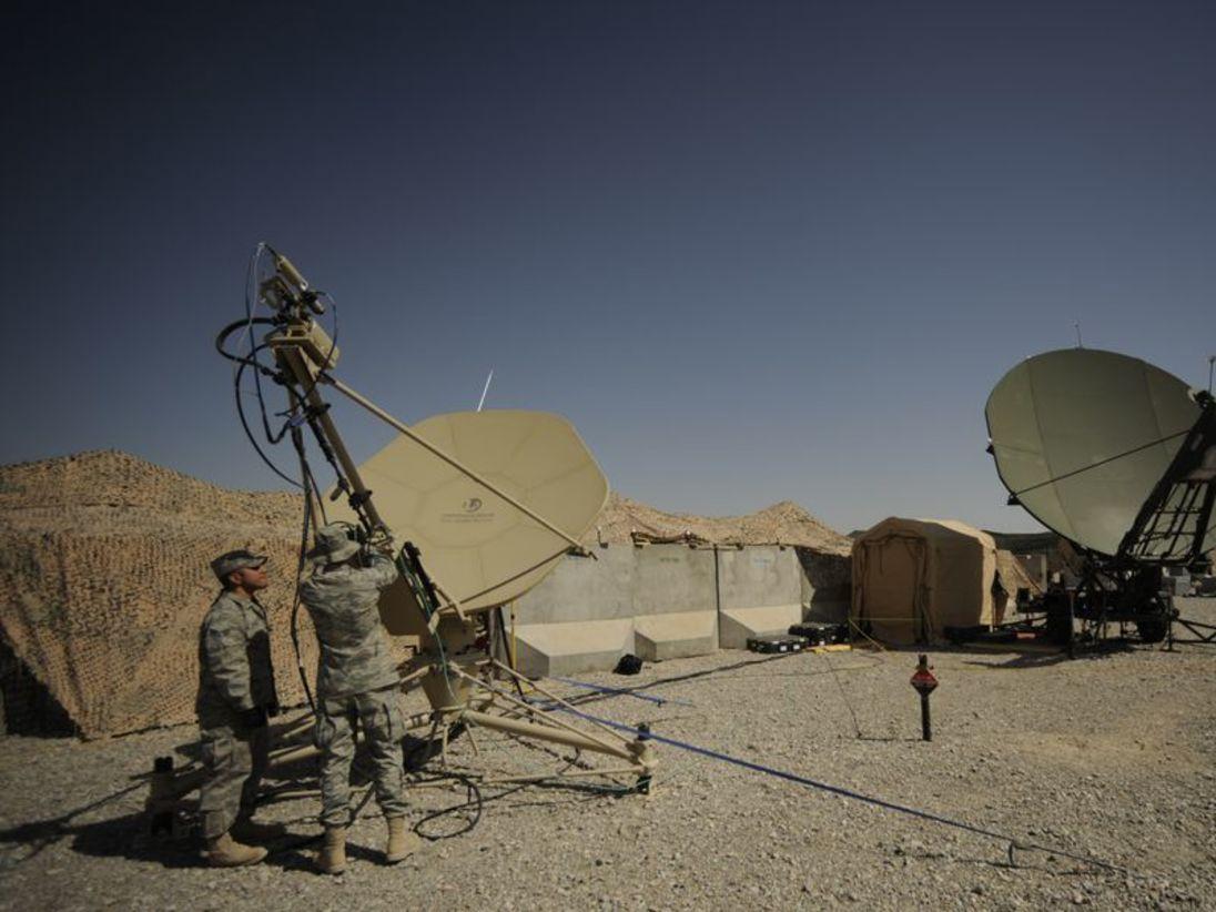 Специалисты по спутниковой связи проводят плановое техническое обслуживание спутниковой антенны на аэродроме Кандагар в Афганистане.