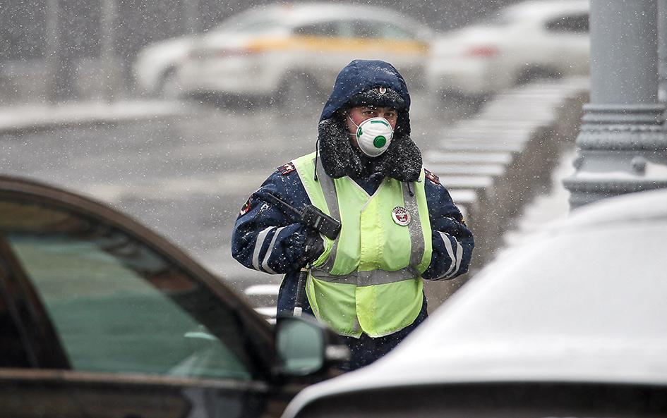 Сотрудник ДПС в респираторе на одной из центральных улиц города
