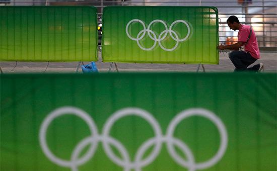 Рабочий крепит эмблему Олимпийских игр науличный барьер вРио-де-Жанейро