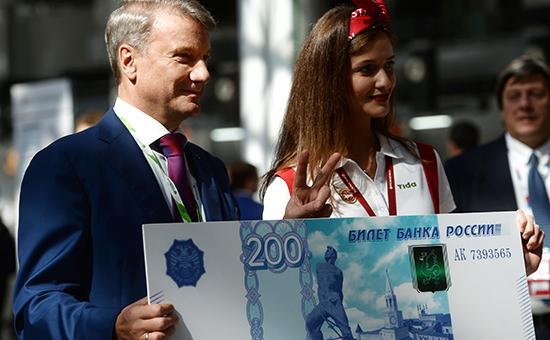 Глава Сбербанка Герман Греф фотографируется собразцом банкноты в200 руб.нафоруме «Сочи-2016», 30 сентября 2016 года