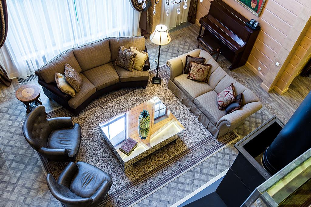 Для напольного покрытия дизайнер использовала керамогранит, объединивший все помещения первого этажа вединое пространство. Декоративные вставки, инкрустированные впол, визуально разграничили его наразные функциональные зоны  На фото: вид на гостиную со второго этажа