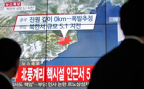 Люди на фоне новостного сюжета о сейсмической активности на ядерном полигоне КНДР. Сеул, Южная Корея