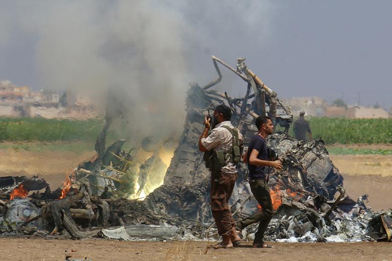 Мужчины осматривают обломки российского вертолета, которыйбыл сбит повстанцами всирийской провинции Идлиб