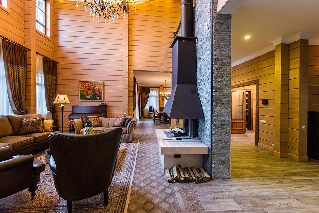 Главное украшение гостиной, выполненной в стиле хай-тек, — камин, спроектированный таким образом, чтобы отделить гостиную от прохода на первом этаже к спальной комнате и лестнице на второй этаже  На фото: гостиная сдровяным камином вцентральной части дома