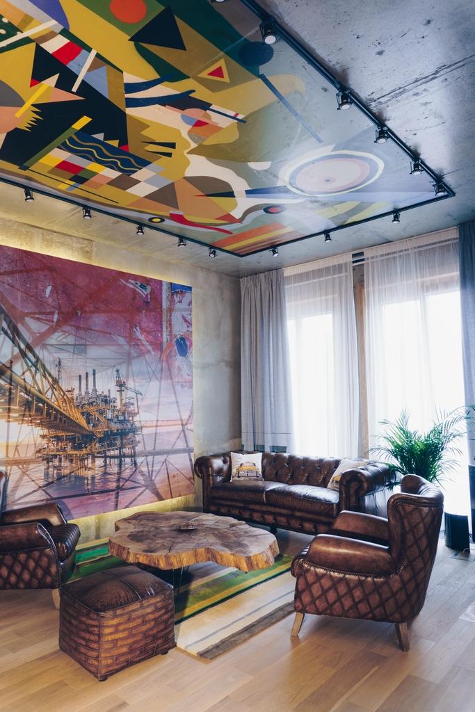 Акустические панели, отвечающие зашумоизоляцию, спрятаны заизображениями наиндустриальную тему врабочей зоне ибольшой переговорной