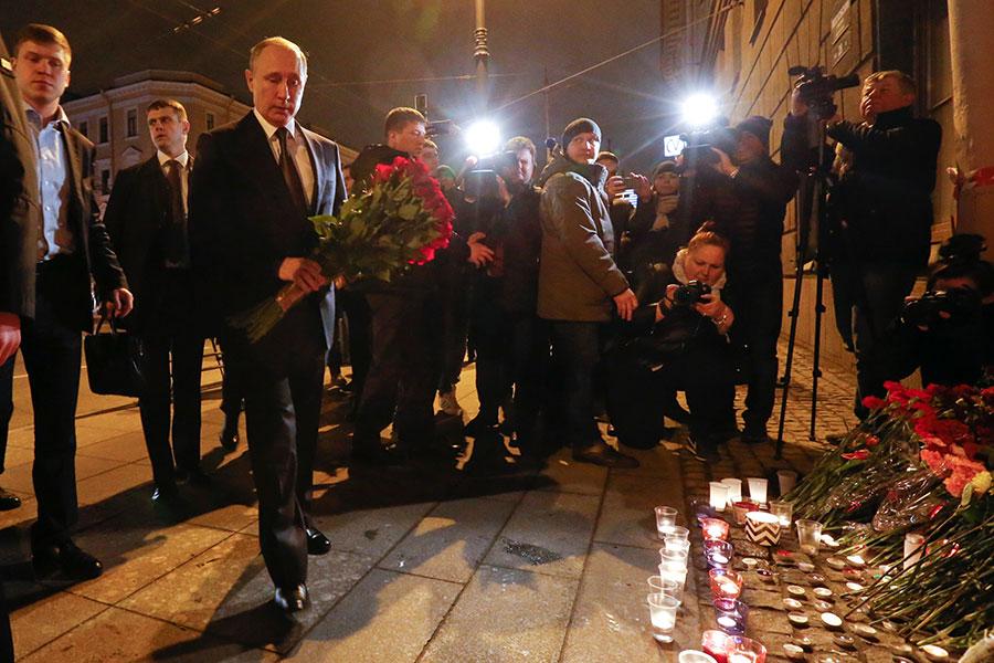 Президент России Владимир Путин (слева напервом плане) возлагает цветы у станции метро «Технологический институт»