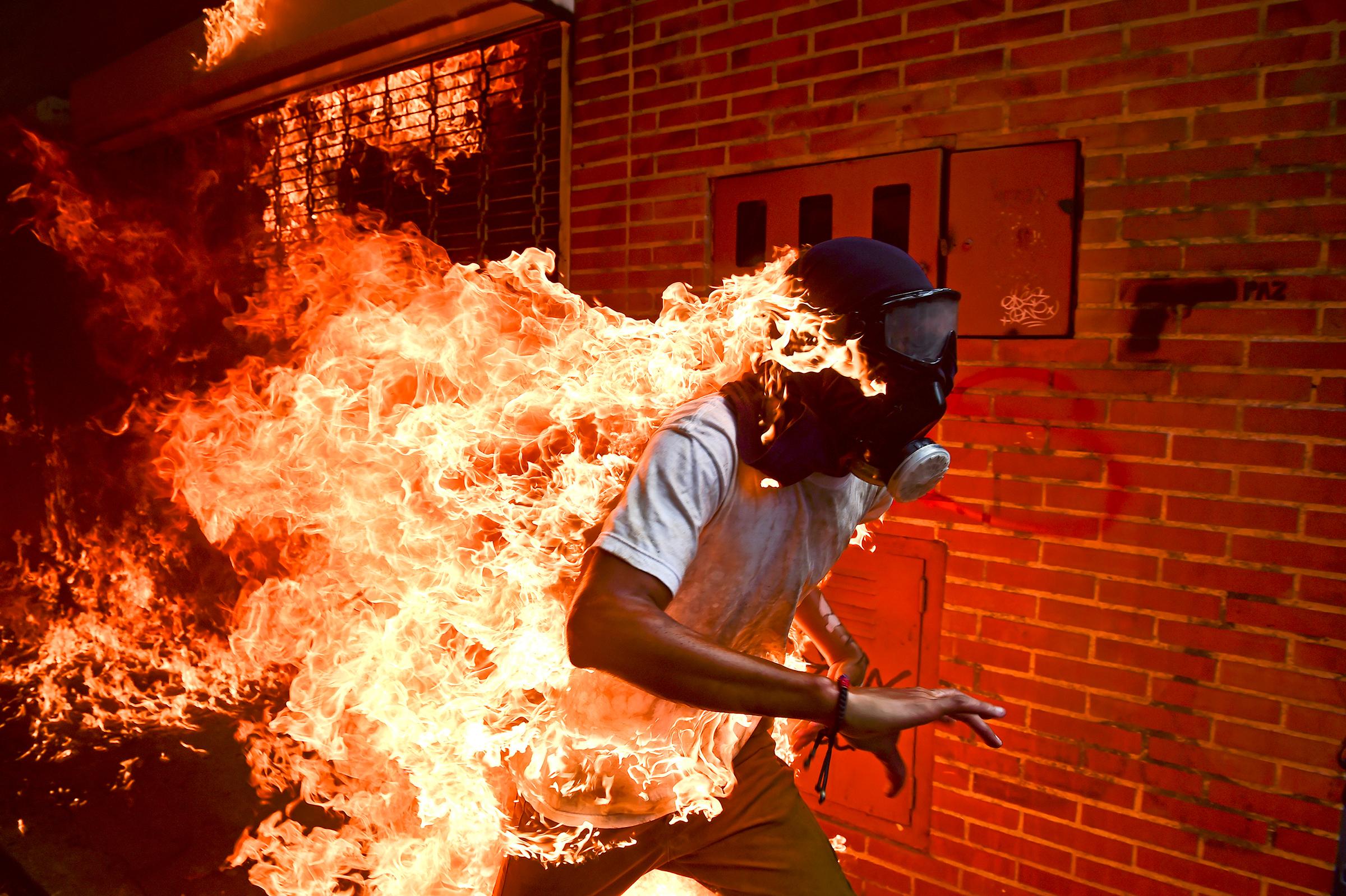 Лучшим снимком признана работа фотографа Роналдо Шемидта «Кризис в Венесуэле». На ней изображен бегущий в противогазе демонстрант, одежда которого охвачена огнем. Фотография сделана 3 мая 2017 года в Каракасе во время митинга против президента Венесуэлы Николаса Мадуро. Онатакже победила в номинации «Главная новость».  По информации The Washington Post, на снимке изображен 28-летний Хосе Виктор Саласар Балса, принимавший участие в антиправительственном митинге в мае 2017 года. На премию в категории «Фотография года» претендовали еще пять работ, в том числе о кризисе в Мьянме, битве за Мосул и теракте в Лондоне.