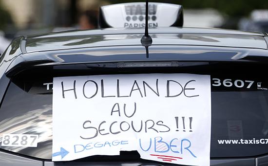 Париж. Надпись наплакате: «Олланд, помоги! Uber— домой!»