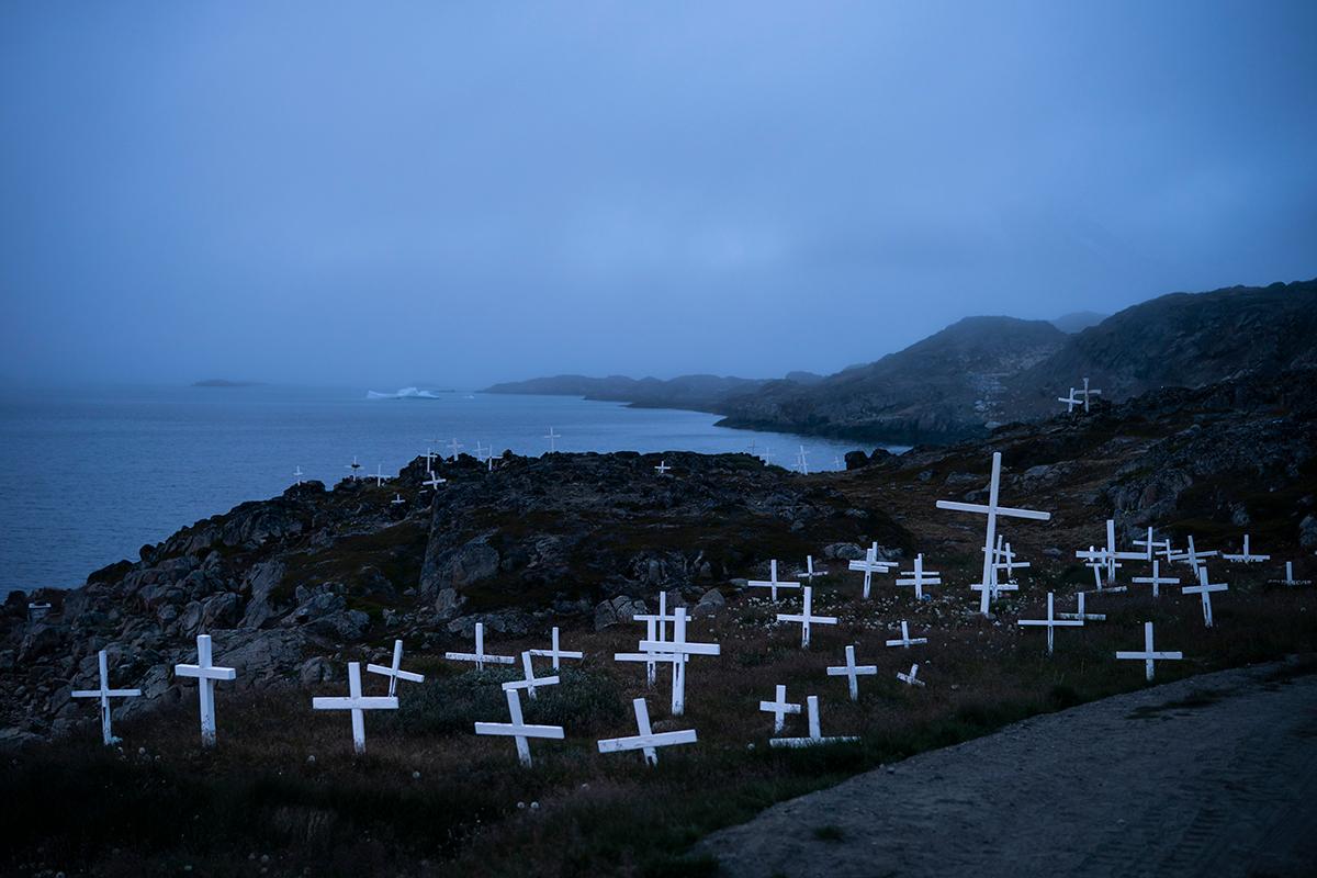 Кладбище поселка Кулусук на фоне плывущего вдали айсберга