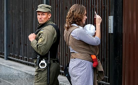 С помощью видеосвязи женщина показывает паспорт служащему посольства РФ вКиеве, чтобыпринять участие ввыборах