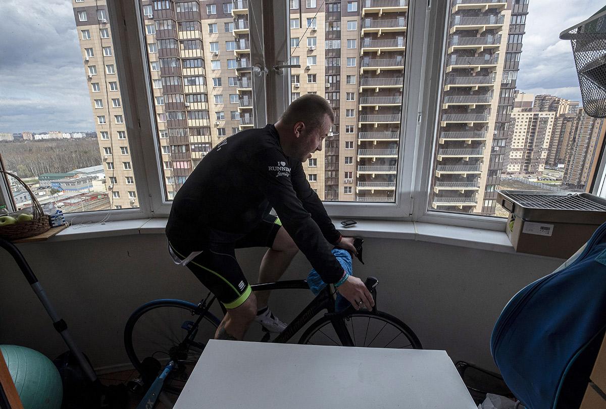 Мужчина тренируется на балконе своего дома во время пандемии коронавируса