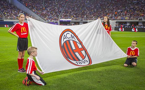 Дети держат флаг ФК «Милан» перед матчем Лиги чемпионов