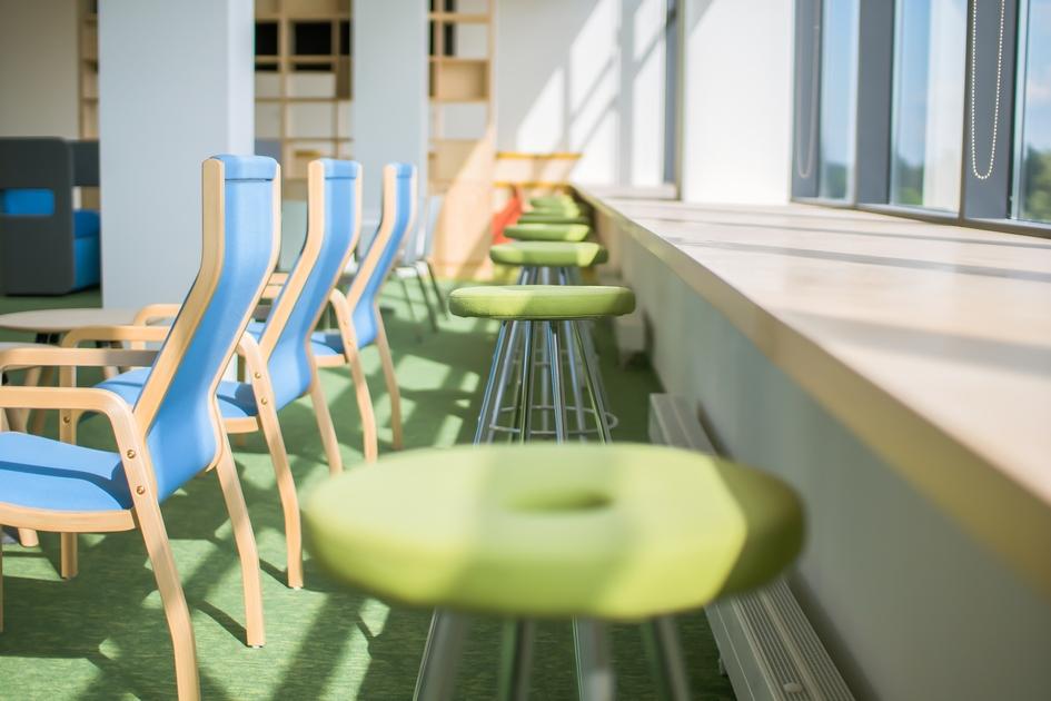 Вдоль стеклянной фасадной стены классов смонтированы широкие деревянные подоконники: на них удобно сидеть и даже лежать. А школьные парты — высокие (110 см), чтобы можно было работать как сидя на высоком стуле, так и стоя