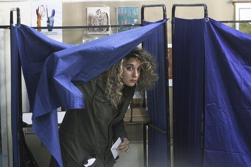 Девушка на избирательном участке в Афинах собирается опустить свой бюллетень в урну.