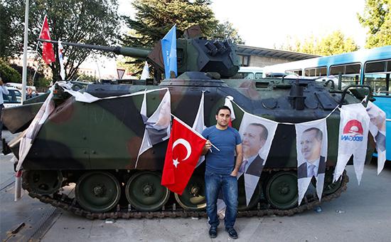 Сторонник действующего правительства позирует у захваченного танка мятежников возлепарламента Турции вАнкаре