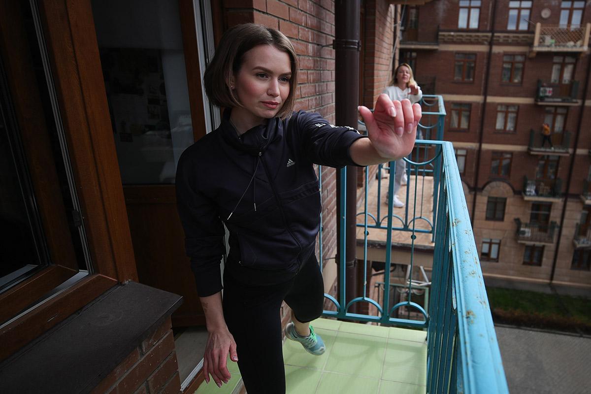 Алена Матросова, живущая в многоквартирном доме на улице летчика Ивана Федорова в Химках, показывает физические упражнения на балконе своей квартиры для жителей дома