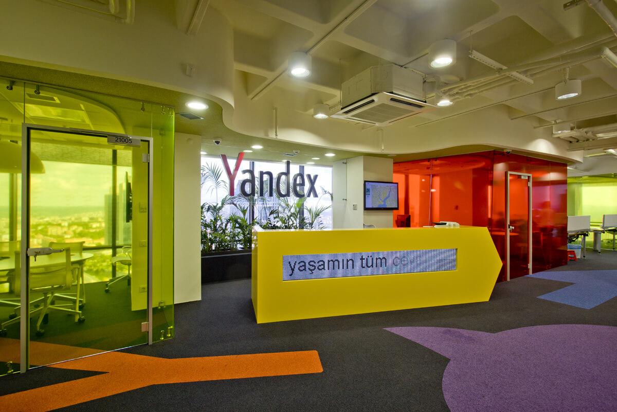 Стамбульский офис «Яндекса» открылся в 2011 году. Интерьер рабочей зоны воспроизводит дизайн-код компании: желтые цвета, много стекла, зеленых растений и непременная стойка ресепшен в виде поисковой строки