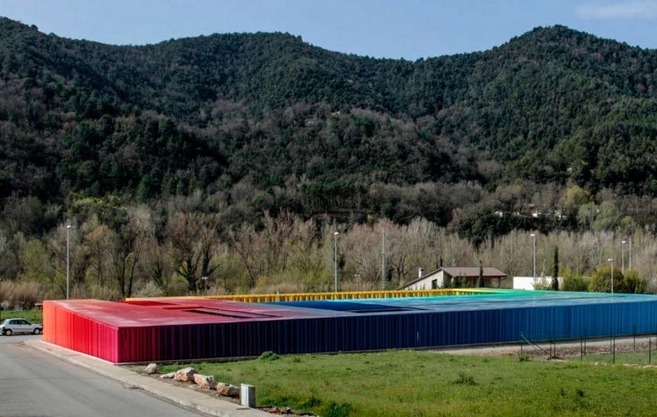 Строгую геометрию здания муниципального детского сада разбавляют разноцветные вертикальные трубки (некоторые из них вращаются) разного диаметра, из которых выполнены фасады