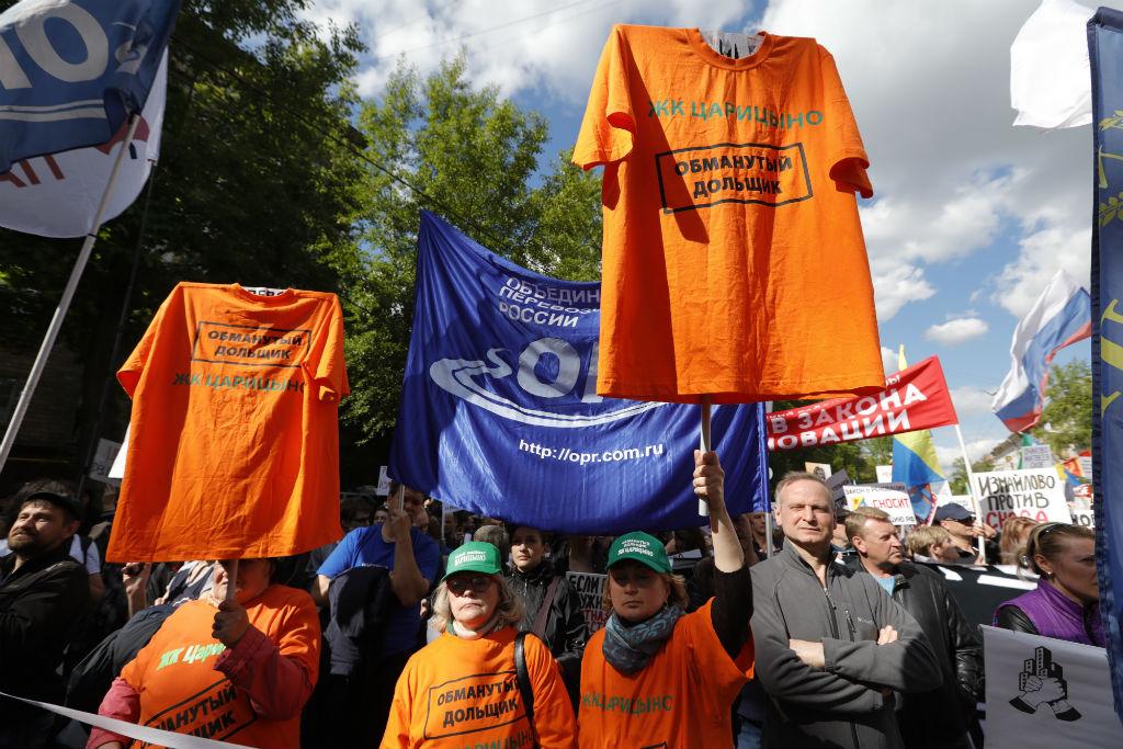 Участники митинга шли подфлагами столичных районов, скрасно-белыми строительными лентами, плакатами итранспарантами