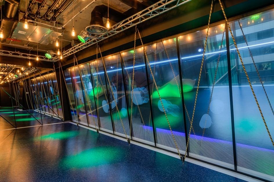 Рабочие зоны разграничены стеклянными и мобильными перегородками-флипчартами, а также двухуровневыми мягкими спальными боксами, напоминающими трюм корабля