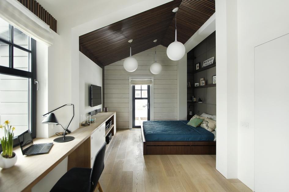 В этом помещении дизайнеры смогли объединить спальню и рабочий кабинет. Функцию последнего выполняет столик у окна в левой нижней части снимка