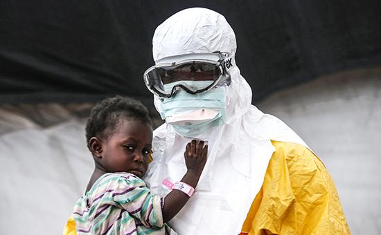 Медицинский работник держит на руках ребенка с подозрением на Эбола