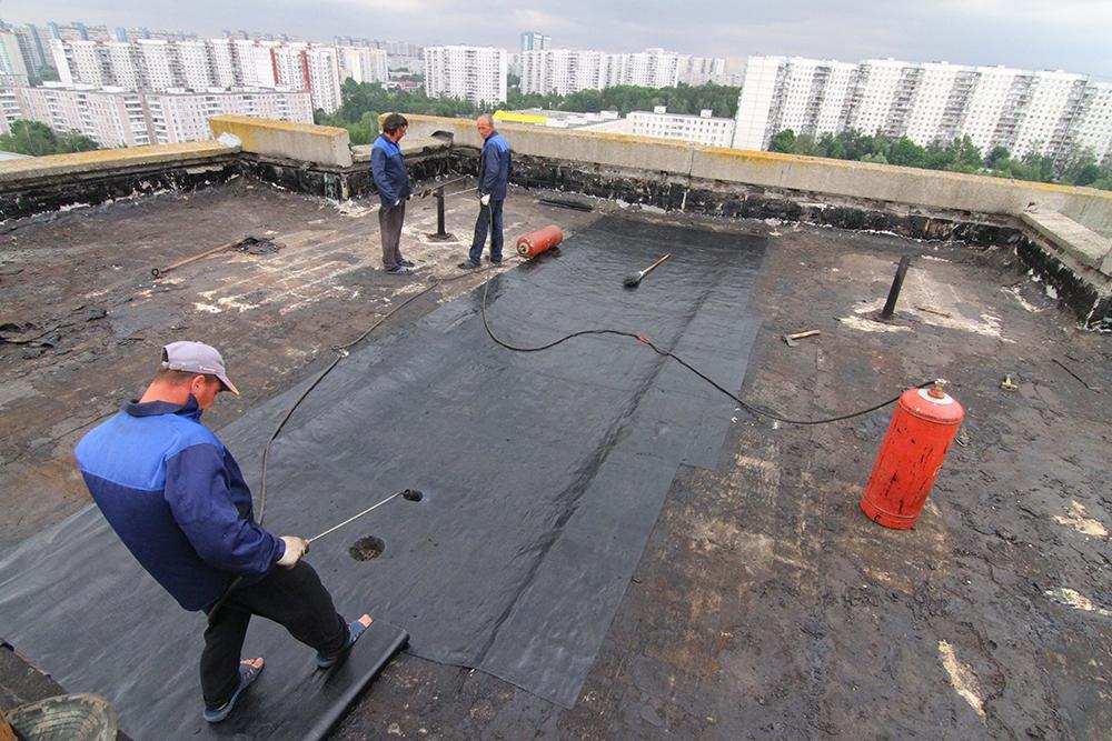 Укладка нового рубероида на крыше во время капитального ремонта многоэтажного панельного дома в Ясенево. Теперь жителям МКД придется платить за это из своего кошелька