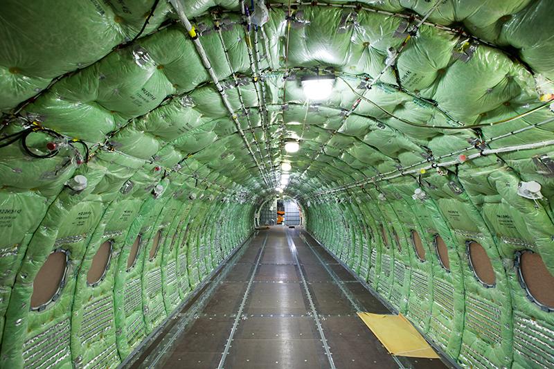 Фюзеляж самолета изнутри обит зелеными матами для тепло- и звукоизоляции