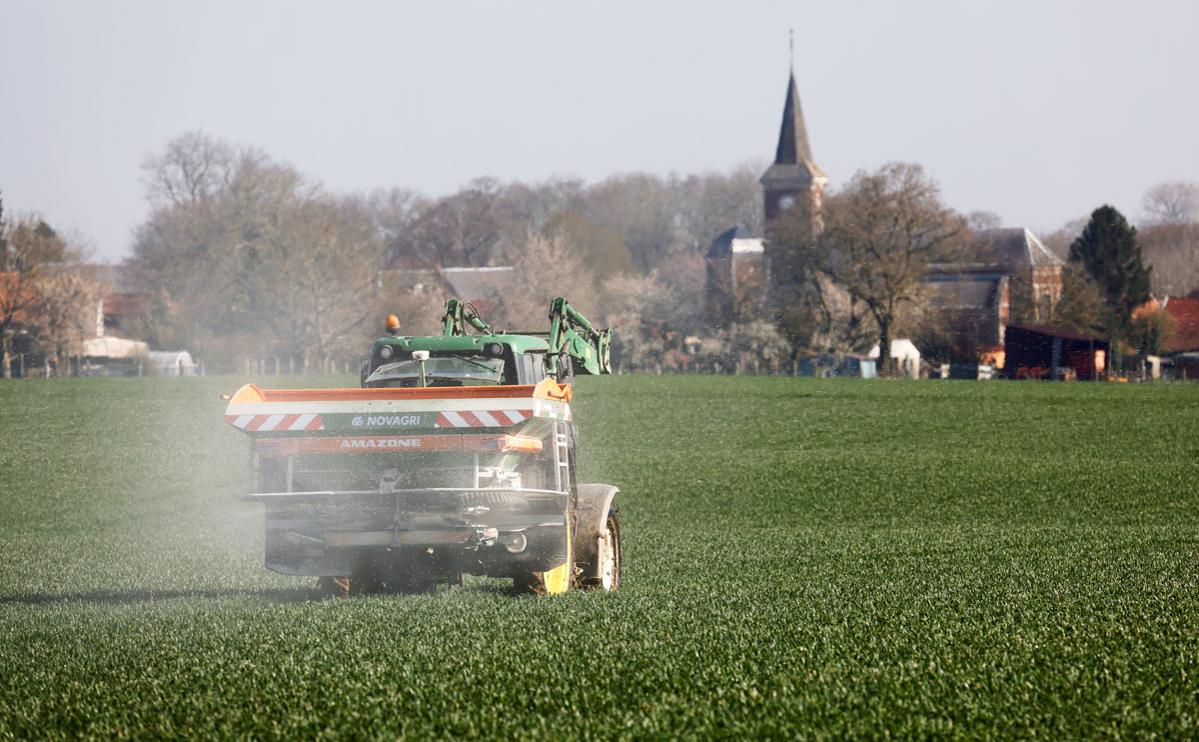 Фермер распыляет азотные удобрения