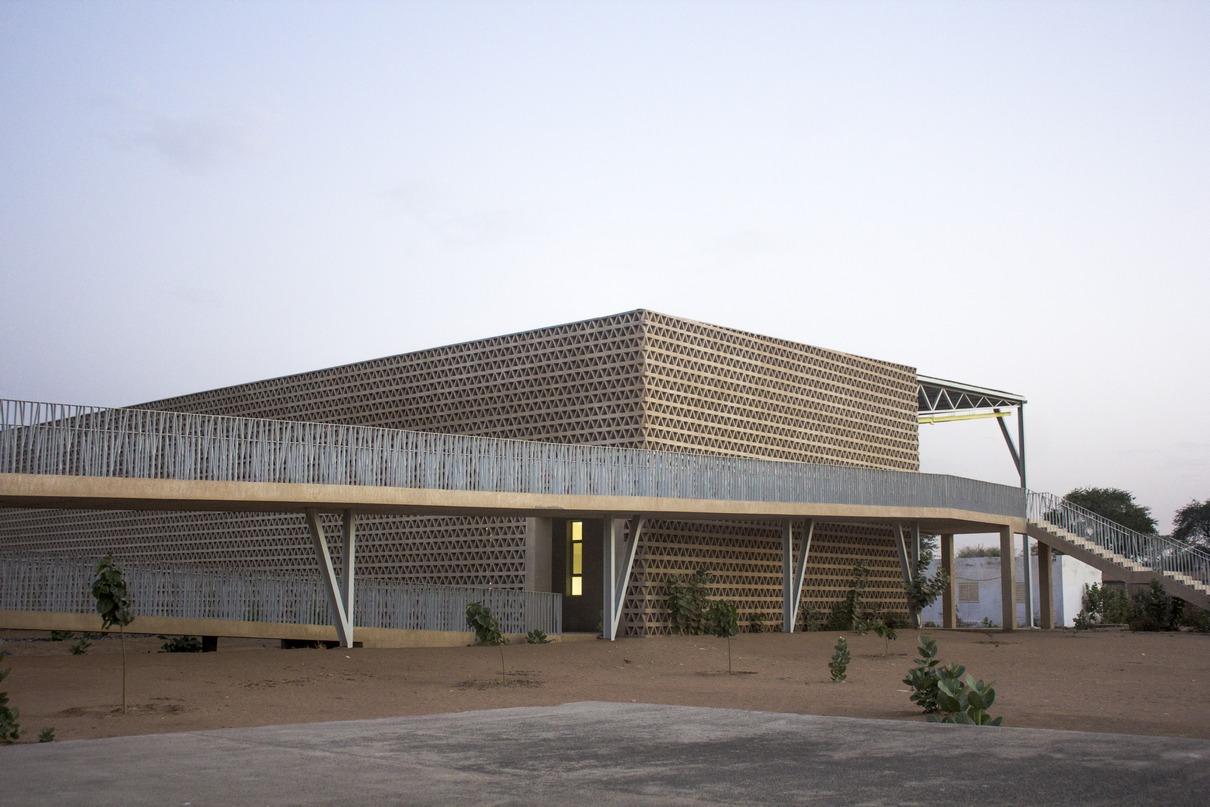В основе проекта испанского архитектурного бюро IDOM— образ дерева, растущего в центре кампуса Университета имени Алиуна Диопа. Спроектированный новый учебный корпус представляет собой своего рода «место под тенью», где студенты могут проводить время после занятий. Защиту от солнца обеспечивает массивный навес и плотные решетчатые стены, а отсутствие водопровода компенсируют дренажные плоты с растениями, которые собирают дождевую воду