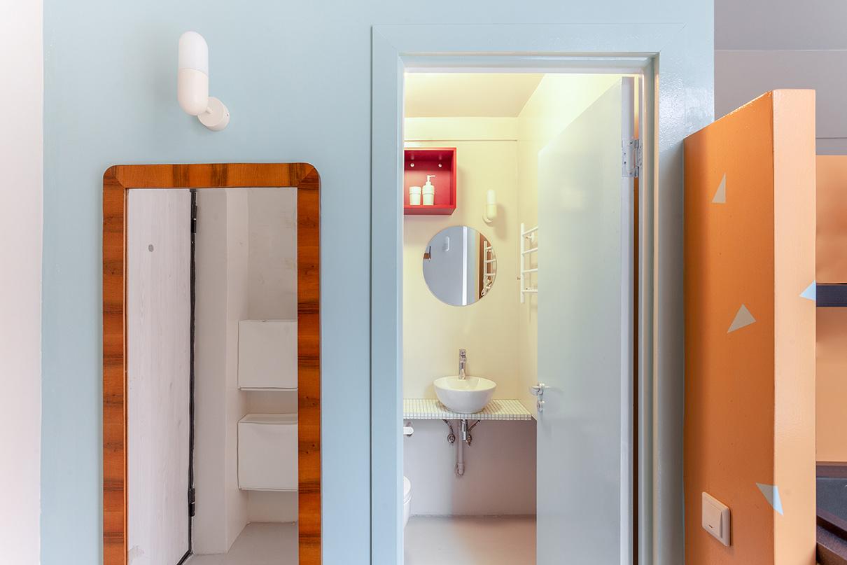 Ванная комната помещена в куб с антресолью для хранения сезонных вещей. За счет подиума устроена ниша для стиральной машины