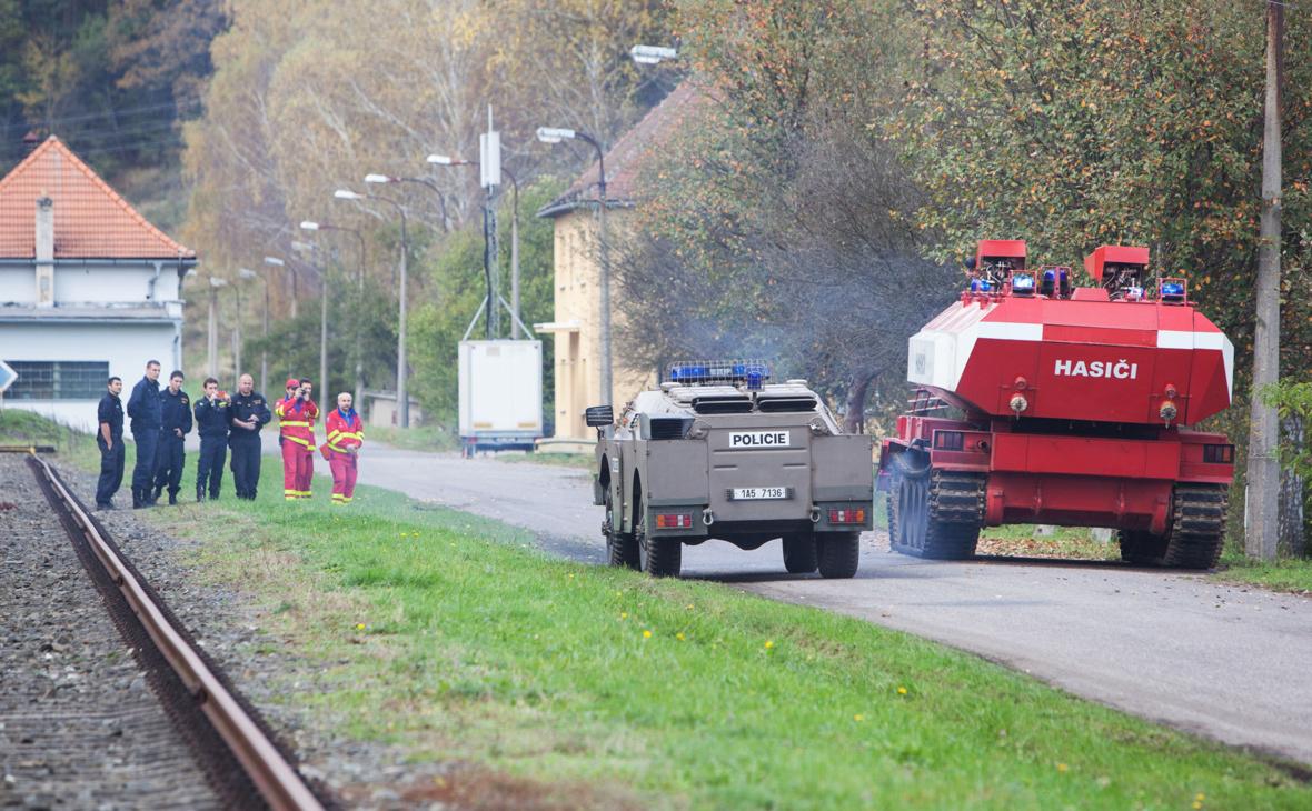 Пиротехники полиции Чешской Республики, вооруженные пожарным танком и военным транспортером, в районе склада боеприпасов в Врбетице, где взрывом было уничтожено одно из зданий, 18 октября 2014