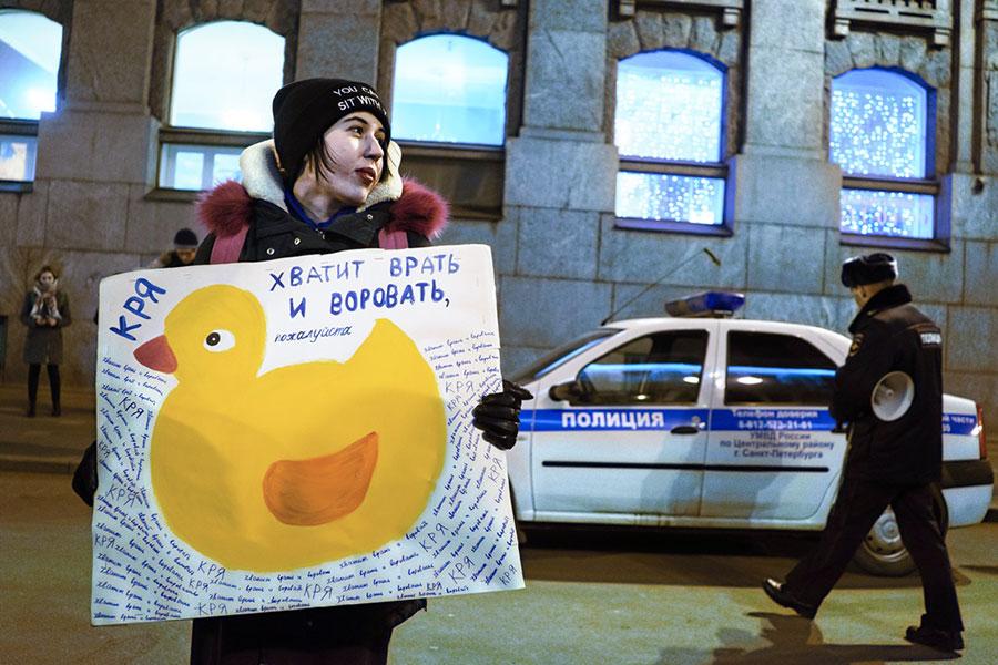Участница акции протеста «Народный сход» заотставку Дмитрия Медведева сплакатом «Хватит врать иворовать». 6 марта 2017 года