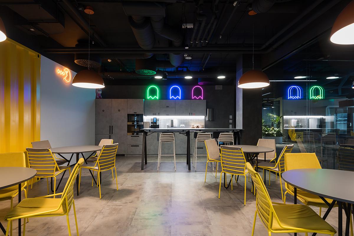 Кофе-поинт с барной зоной и несколькими столами выполнен в желтом цвете. Над кухонной зоной установлены неоновые вывески