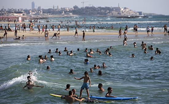 Израильтяне и туристы отдыхают на пляже Средиземного моря в Тель-Авиве, Израиль