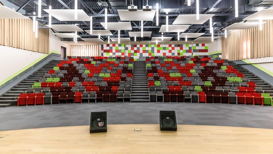 Вместо стандартного актового зала в школе построен амфитеатр со сценой. Стены, потолок и кресла обиты специальным шумопоглощающим материалом, препятствующим образованиюэха, благодаря чему выступающего слышно без микрофона. Зал также оснащен радиоузлом, дикторской комнатой, гримерками и двумя проекторами, транслирующими изображение на стену