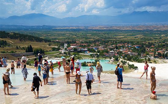 Туристы наприродном объекте Памуккале в Турции