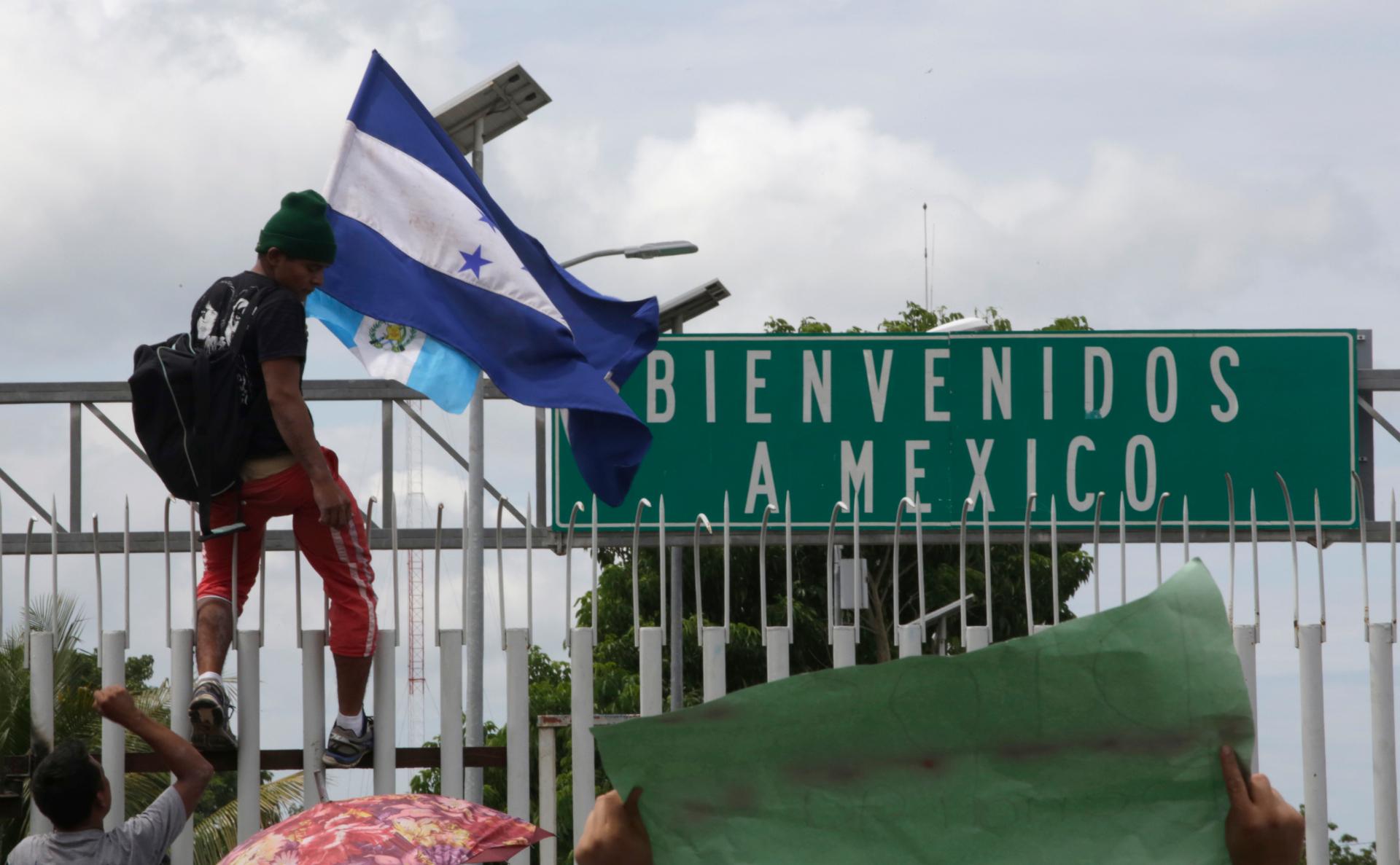 Мигрант из Гондураса с национальным флагом страны на границе с Мексикой