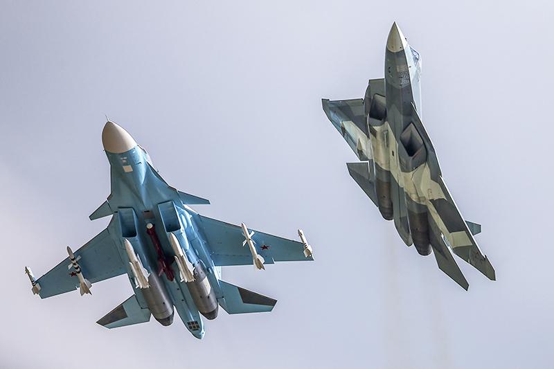 Су-34  Самый современный российский самолет, участвующий воперации внебе надСирией,— истребитель-бомбардировщик Су-34. Он такжеклассифицируется какфронтовой бомбардировщик, таккакспособен наносить точные удары нетольковтактической, нои воперативной глубине территории противника. Официально самолет принят навооружение тольков2014 году, норазрабатывался еще сконца 1980-х. Некоторые эксперты приписывают Су-34 участие ввойне вЮжной Осетии в2008 году. Среди достоинств—высокая маневренность нанизких высотах, титановая кабина, защищающая экипаж издвух пилотов, современное навигационное, прицельное оборудование ирадар. Развивает скорость до1900 км/ч. Максимальная дальность— 4500км бездозаправки, потолок—более 14тыс. м надуровнем моря. 12 точек подвески позволяют нести до8 т боеприпасов. По официальным сообщениям Минобороны, вСирии Су-34 использует корректируемые 500-килограммовые бомбы КАБ-500 иракеты Х-29Л слазерным наведением. Пока нароссийской авиабазе вЛатакии были замечены шесть подобных машин.  На фото: Фронтовой бомбардировщик Су-34 ироссийский многоцелевой истребитель пятого поколения—перспективный авиационный комплекс фронтовой авиации (ПАК ФА) Т-50 (слева направо)
