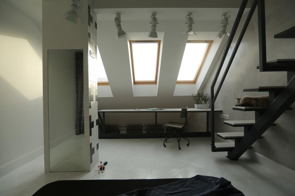 Напротив постели у окна расположено рабочее место, подсвеченное софитами. Лестница ведет в мини-библиотеку, спрятанную под самой крышей